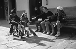 "Feature Picture Story: """"Slow Down!"" A brother and sister speed past their mother, grandmother and great grandmother on their tricycles while playing in the streets of Corniglia, Italy."