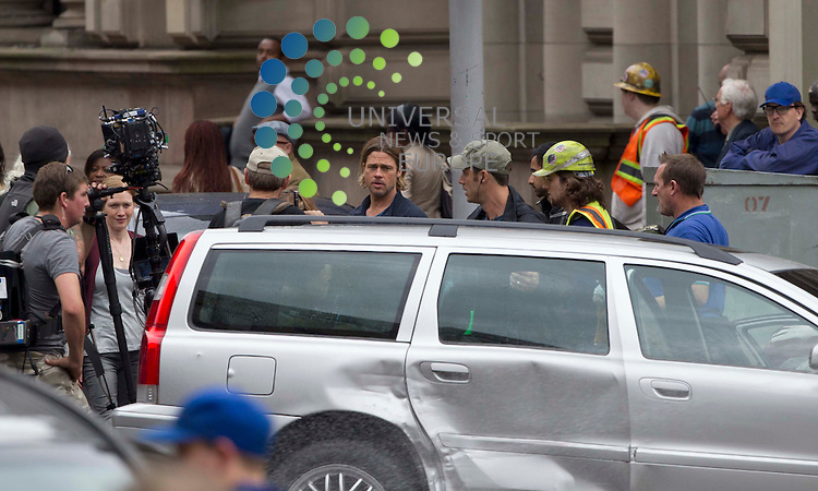 Glasgow, Scotland - Brad Pitt with his on set family run from a car during a seen from the film World War Z..Picture: Maurice McDonald/Universal News And Sport (Scotland). 24 August 2011. www.unpixs.com..