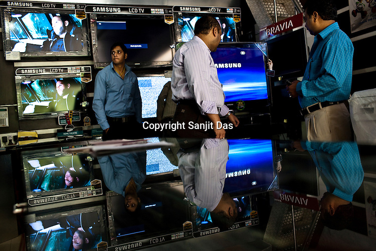 Manish Gupta (centre) attempts to make a sale of a latest flat screen television to one of his customers at Gupta Store in Kailash Colony Market in New Delhi, India.