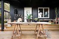 Under the covered terrace are a number of tables designed by Jimmy Schoenning Hem, accompanied by cushions sewn out of an Ikea rug, a bottle holder bought at a farmers' auction and a hanging lantern by Rydens
