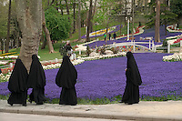 Nuns are among the visitors exploring a city park where springtime tulip blooms abound in Istanbul.