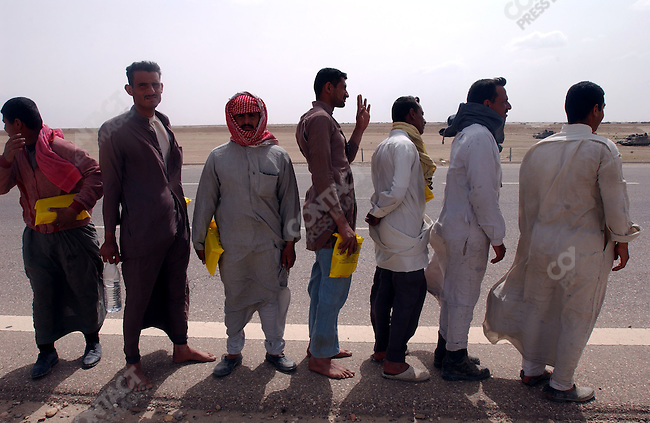 Iraqi men, travelling on the road to Baghdad near Basra, were stopped and searched as well as given MRE rations by American soldiers.  Here they lined up prior to being searched. March 22, 2003