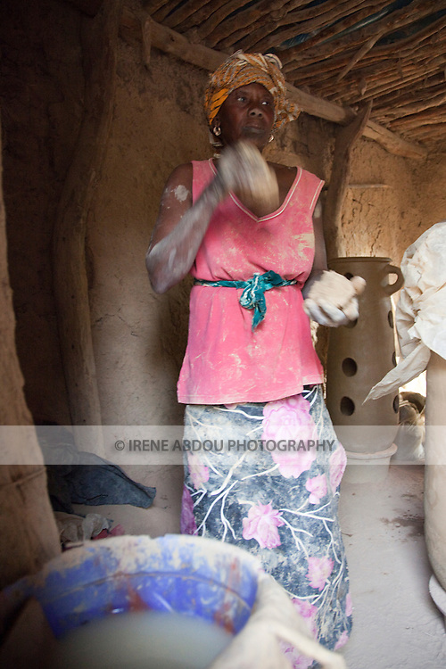 In the village of Kalabougou near Segou, Mali, women of the numu blacksmiths population have worked for centuries as traditional potters.  A woman skillfully throws the clay between her hands as she works to mold a tall, thin pot half her size.
