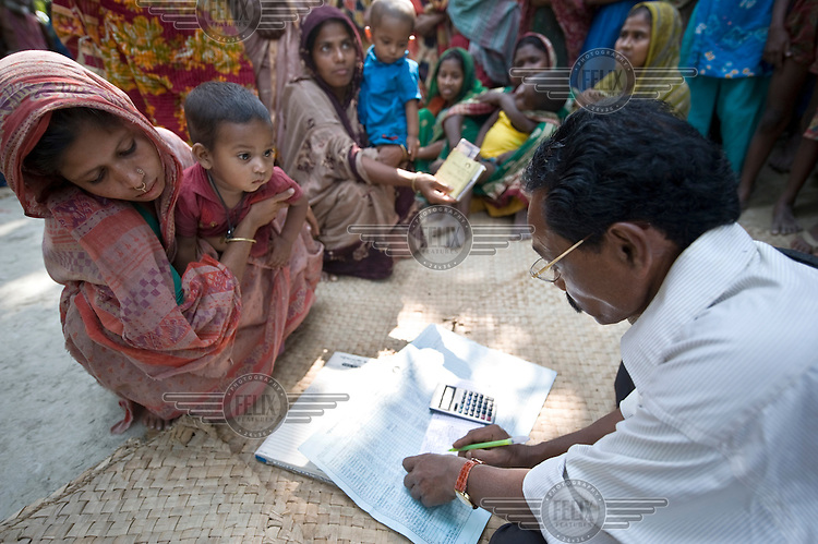Women and children gather for the visit of an employee of the Patuakhali Development Centre who has travelled to this small village on one of the islands in the delta to receive the monthly instalments of loan re-payments and to grant new loans. This microcredit scheme was initiated by a local NGO supported by Terre des Hommes, a Dutch NGO..