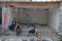 Residents sit at an empty shop at Dawangjing Village which is being demolished on April 9, 2009 on the outskirts of Beijing, China. The local authorities are evicting residents, who are mainly migrant workers, to redevelop the area. The redevelopment of Beijing continues in high speed.
