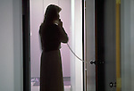 Silhouette of anxious woman on telephone in hospital