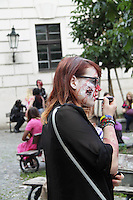 female participant to the prague zombie walk may 2014 is preparing her make up just before the walk starts.