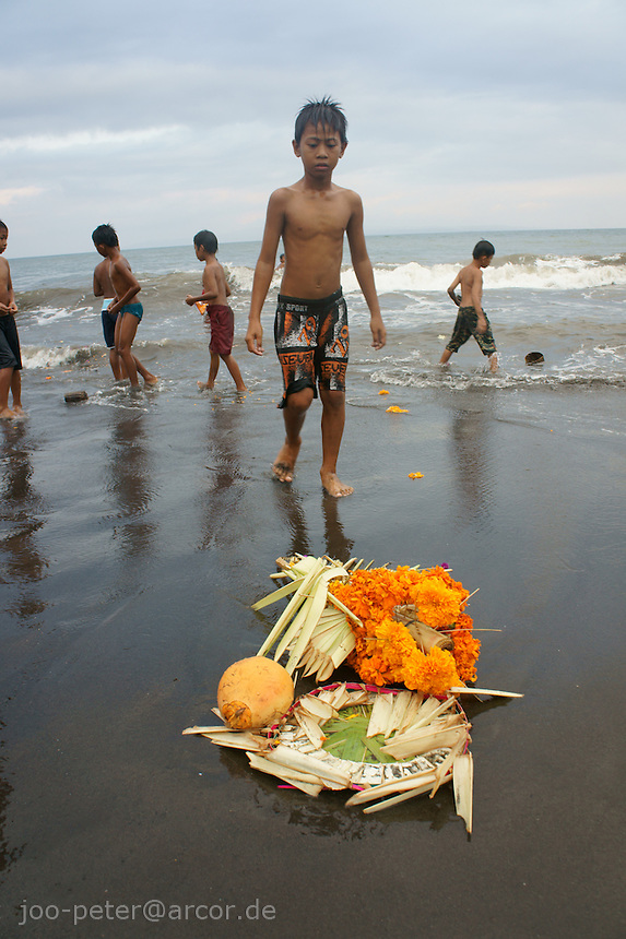 child is curious about reminders of the cremation ceremony, after the decorated,  golden throne with  ashes of the passed family member were thrown in to the sea just before,  cremation ceremonies  September 17th 2011,  family  Budiana and others, coming from Banjar Pande, Peliatan, Bali, Indonesia. Cremation ceremonies in Bali guide the spirit of the passed family member from underworld death realms to divine heavenly nature spirit life circle uprise of the death, becoming a divine ancestor to be reborn in the next generation of the family