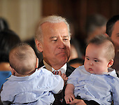 Washington, D.C. - May 1, 2009 -- United States Vice President Joseph Biden holds some babies as he attends the ceremonial swearing-in of Commerce Secretary Gary Locke and Health and Human Services Secretary Kathleen Sebelius in the East Room of the White House in Washington, D.C. on Friday, May 1, 2009. <br /> Credit: Ron Sachs / CNP