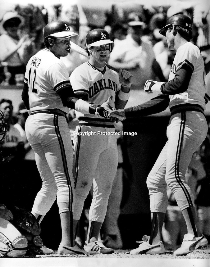 Oakland Athletics Dave Kingman gets congrats at home from Dusty Baker and Mike Heath after home run with Baker aboard. (1985 photo by Ron Riesterer)