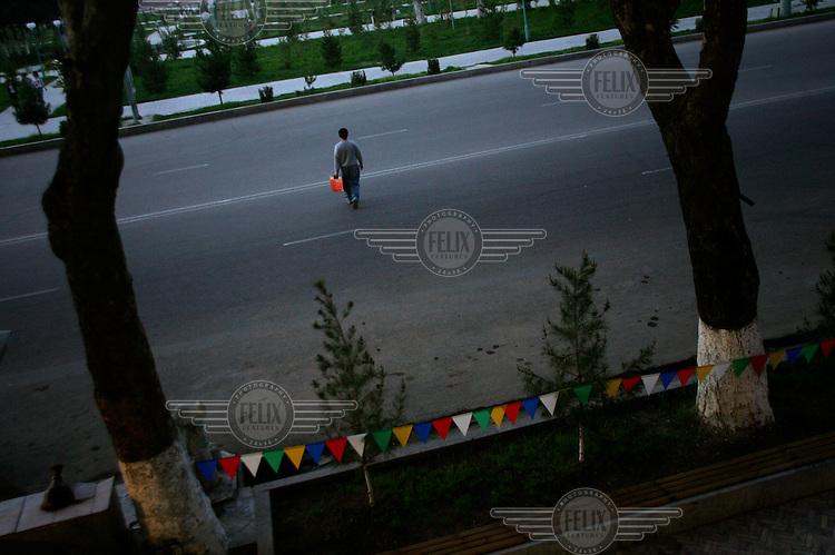 A man crosses an empty road.