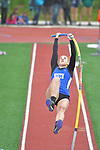A pole vaulter on her way up to the bar.