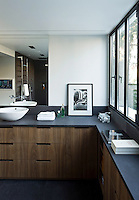 This contemporary bathroom benefits from large windows overlooking the garden and is furnished with a grey slate work surface and banks of fitted drawers