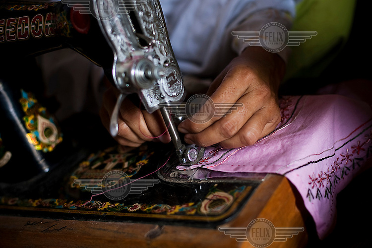 A woman learns to use a sewing machine at a vocational training centre for people affected by the major flooding that hit Sindh in 2011.