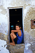 Itaparica Island, Brazil. Afro-Brazilian boy sitting wedged in a dilapidated doorway. Bahia State.