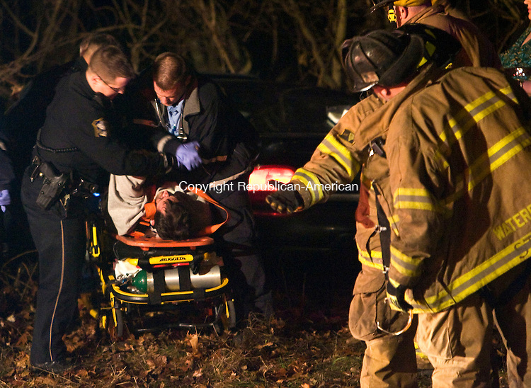 WATERBURY, CT - 15 DECEMBER 2008 -121508JT11-<br /> Waterbury firefighters watch as policemen and paramedics try to restrain a belligerent man who was just extricated from a vehicle involved in an accident on Monday night on Sunnyside Avenue near Riverside Street.<br /> Josalee Thrift / Republican-American