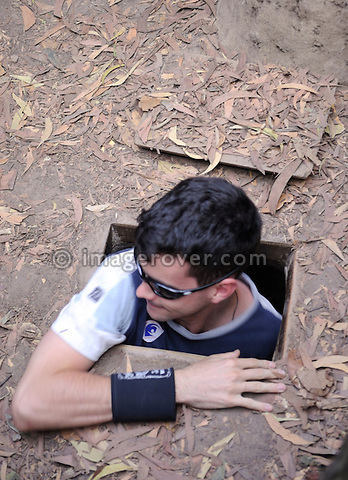 Asia, Vietnam, Cu Chi nr. Ho Chi Minh City (Saigon). Cu Chi Tunnels. Tourist entering a typical small and camouflaged tunnel entrance. Tunnel complexes have been used by the Vietnamese for centuries, they were a key part of guerilla warfare during the Vietnam War and played  major role in defeating US American soldiers.