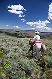 USA, Wyoming, Encampment, a cowboy rides his horse through the sage brush landscape, Abara Ranch