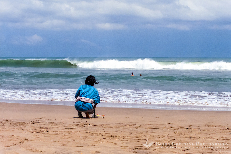 Bali, Badung, Kuta. A balinese woman placing her offerings on the beach.