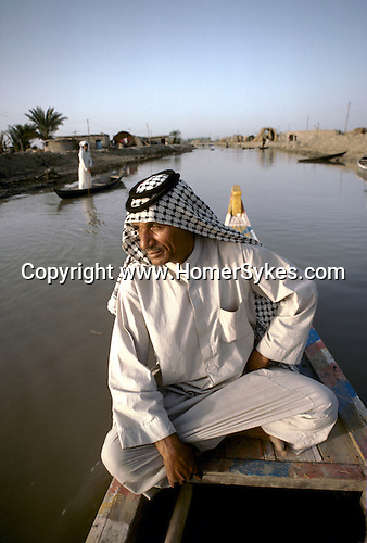 Marsh Arabs. Southern Iraq. Circa 1985. Marsh Arab man in boat with  adobe homes  banks of river Tigris. Haur al Mamar or Haur al-Hamar marsh collectively known now as Hammar marshes Irag 1984