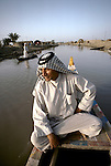 Marsh Arabs. Southern Iraq.  Marsh Arab man in boat with  adobe homes  banks of river Tigris. Haur al Mamar or Haur al-Hamar marsh collectively known now as Hammar marshes Iraq 1984