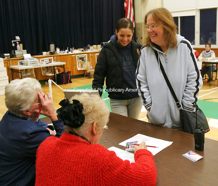 NAUGATUCK, CT,  07 NOVEMBER 2006, 110706BZ01- Checkers Barbara Szczesiul (CQ), left, and Dorothy Smith, (seated) check the identification of Nina Green, of Naugatuck, and her mother Laurie Integlia, of Naugatuck, during voting at Western School Tuesday afternoon. <br /> Jamison C. Bazinet Republican-American