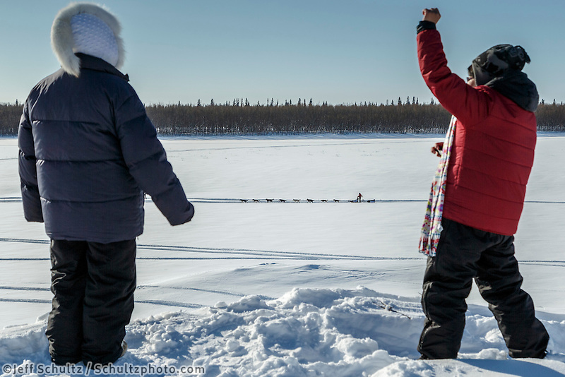 Huslia residents cheer on departing teams from the bank of the Koyukuk river in the afternoon at the Huslia checkpoint on Saturday  March 14, 2015 during Iditarod 2015.  <br /> <br /> (C) Jeff Schultz/SchultzPhoto.com - ALL RIGHTS RESERVED<br />  DUPLICATION  PROHIBITED  WITHOUT  PERMISSION