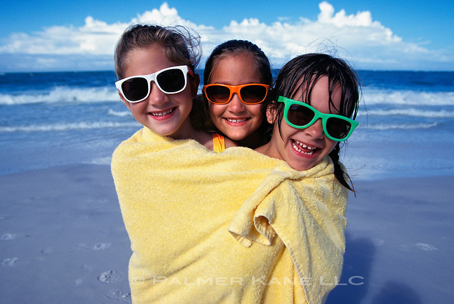 Three Girls With Sunglasses Wrapped In Blanket At Beach