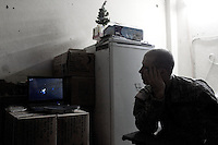 a US soldiers from 1st platoon Alfa company, 3-103d armor regiment, 28th US National Guard Division watches the movie American wedding for the tenth time since his deployment in Iraq  while on a three day rotation on OP ( observation post) HOTEL, a five floors building in Western Ramadi, capital of the Anbar province, Iraq on the day following the national elections FRI DEC 16th 2005..Nor US military or Iraqi Army  were in charge of securing the Ramadi polling stations during the elections. they simply conducted daily routine patrols hoping that the insurgency would keep its promise not to attack on this day. US forces watched the voting form observation posts located at the boarder of the city. OP HOTEL is one of them on code name route MICHIGAN. On August 15 2005 a suicide bomber detonated a truck filled with more than 500 KGs of explosives in front of the main entrance. Due to heavy fortification no US soldiers suffered deadly wounds. The OP scans a strip of road on which more than 60 improvvised explosive devices are found or detonated every month. life at the HOTEL is quite simple. US squads rotate on the numerous observation posts in the building every six hours for three hours. sniper teams keep the area constantly in their rifle scopes. it's a 24 hour, non stop process. hot meals are driven by platoon members once a day. living conditions are miserable. the worst part of it all is being trapped in a fortified buliding, where the only windows available are the ones out of which they  shoot all their weapons. these soldiers saw the elections through these holes, with their body armors and their night vision nodes, through their rifle scopes and with the constant soundtrack of bombs, mortars and small arms fire always present in the background.