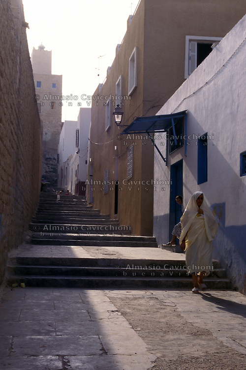 Tunisia, citt&agrave; di Kairouan, donna in abiti tradizionale in una strada della Medina.<br /> Tunisia, the city of Kairouan, woman in traditional clothes in a street in the Medina.