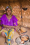 "A woman in the small village of Bele Kwara in southwestern Niger cooks ""fari masas"" inside her traditional straw house.  The fari masas will be dipped in a bit of sugar and eaten for breakfast."