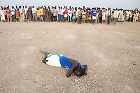 The winner of the 1500m collapses on the ground at the Twic Olympics in Wunrok, Southern Sudan.