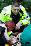 © Joel Goodman - 07973 332324 . 16 August 2013 . Manchester , UK . 15 year old named Connor , wearing a tag , being tended to by paramedics aided by Inspector Bailey-Smith and a passing breast surgeon (red hair, Cliona Kirwan - 07970 058522 ) , after suffering a severe leg break in Wythenshawe Park following a motorbike crash . Drive along with Inspector Matt Bailey-Smith ( 16366 ) of Greater Manchester Police 's Serious Collision Unit . Photo credit : Joel Goodman