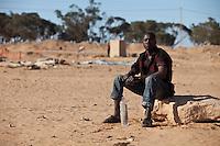 Tunisie RasDjir Camp UNHCR de refugies libyens a la frontiere entre Tunisie et Libye  refugees camp  Tunisian and Libyan border  ....Tunisia campo profughi di Djiba al confine tra tunisia e Libia  refugie centre africain assis avec une bouteille d'eau ....african refugee sit, with a bottle of water....rifugiato centrafricano seduto , con una bottiglia di acqua