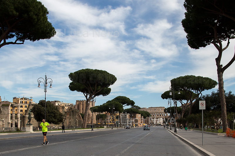"""Outdoor physical activity : allowed but with restrictions.<br /> <br /> Via dei Fori Imperiali.<br /> <br /> Rome, 12/03/2020. Documenting Rome under the Italian Government lockdown for the Outbreak of the Coronavirus (SARS-CoV-2 - COVID-19) in Italy. On the evening of the 11 March 2020, the Italian Prime Minister, Giuseppe Conte, signed the March 11th Decree Law """"Step 4 Consolidation of 1 single Protection Zone for the entire national territory"""" (1.). The further urgent measures were taken """"in order to counter and contain the spread of the COVID-19 virus"""" on the same day when the WHO (World Health Organization, OMS in Italian) declared the coronavirus COVID-19 as a pandemic (2.).<br /> ISTAT (Italian Institute of Statistics) estimates that in Italy there are 50,724 homeless people. In Rome, around 20,000 people in fragile condition have asked for support. Moreover, there are 40,000 people who live in a state of housing emergency in Rome's municipality.<br /> March 11th Decree Law (1.): «[…] Retail commercial activities are suspended, with the exception of the food and basic necessities activities […] Newsagents, tobacconists, pharmacies and parapharmacies remain open. In any case, the interpersonal safety distance of one meter must be guaranteed. The activities of catering services (including bars, pubs, restaurants, ice cream shops, patisseries) are suspended […] Banking, financial and insurance services as well as the agricultural, livestock and agri-food processing sector, including the supply chains that supply goods and services, are guaranteed, […] The President of the Region can arrange the programming of the service provided by local public transport companies […]».<br /> Updates: on the 12.03.20 (6:00PM) in Italy there 14.955 positive cases; 1,439 patients have recovered; 1,266 died.<br /> <br /> Footnotes & Links:<br /> Info about COVID-19 in Italy: http://bit.do/fzRVu (ITA) - http://bit.do/fzRV5 (ENG)<br /> 1. March 11th Decree Law http://bit.do/fzREX (I"""