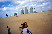 PUNTA DEL ESTE, URUGUAY††- MARCH 2005:  People enjoy the beach and a burried sculpture of a hand in Punta del Este, Uruguay.  (photo by Landon Nordeman)