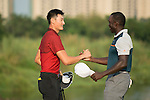 Li Haotong of China (in red) shakes hands with Dwight Yorke (in blue) at the end of their game during the World Celebrity Pro-Am 2016 Mission Hills China Golf Tournament on 23 October 2016, in Haikou, Hainan province, China. Photo by Marcio Machado / Power Sport Images