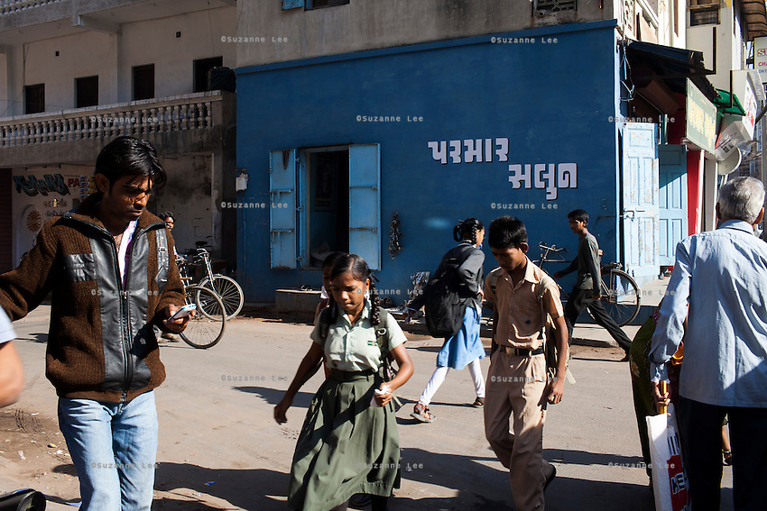 Children return from school as people go about their daily lives outside the Akanksha Infertility Center in Anand, Gujarat, India on 12th December 2012.  Photo by Suzanne Lee / Marie-Claire France