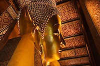 The gilded head of the largest RECLINING BUDDHA in THAILAND (46 meters long) which is found at the THERAVADA BUDDHIST TEMPLE of WAT PO - BANGKOK, THAILAND