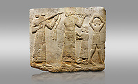 Picture &amp; image of Hittite monumental relief sculpted orthostat stone panel of Procession. Limestone, Karkamıs, (Kargamıs), Carchemish (Karkemish), 900-700 B.C. Anatolian Civilisations Museum, Ankara, Turkey.<br /> <br /> Musicians. Two musicians with short arms, wearing long dresses and wide belts; one plays a Saz (a stringed musical instrument) with tassels on the handle while the other plays the flute. The third small figure holds castanets (?) in his hands. The figure on the right wears a short skirt, contrary to the others. She dances over her finger tips with her hands over her head. <br /> <br /> Against a gray background.