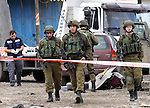 Israeli security forces gather at the site of a car ramming attack in the village of Hawara near the West Bank city of Nablus, on December 31, 2015. A Palestinian drove his car into Israeli forces before being shot dead, the Israeli army said. Israeli medical services said they were treating a soldier who was lightly wounded. Photo by Nedal Eshtayah