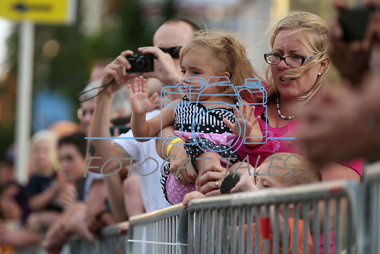 Pam Martinez, of Fernley, Nev., and her daughter Isabella, 3, watch classic cars cruise in downtown Reno, Nev., on Wednesday night, Aug. 7, 2013, during the official Kick-Off Cruise of Hot August Nights. (AP Photo/Cathleen Allison)