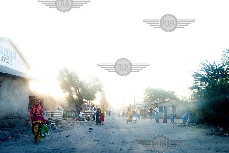A woman walks down a street in Dar Es Salaam.
