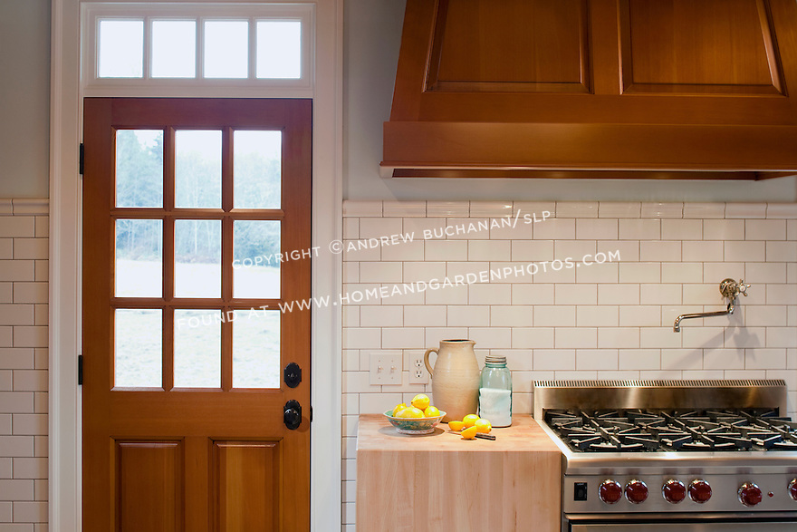 In the kitchen, running bond subway tile, three-over-three lights in the door, the transom window lights above the door, and the massive butcher block chopping black adjacent to the professioanl six burner range all add to the sense of geomoetry, order, and calm of this new contemporary home built in a clean, traditional Shaker style.  The homeowner is a cabinetmaker with a Master's degree in art who designed the house and crafted all of the cabinetry, built-ins, and most other woodwork himself.  The pottery jug is one of his creations.