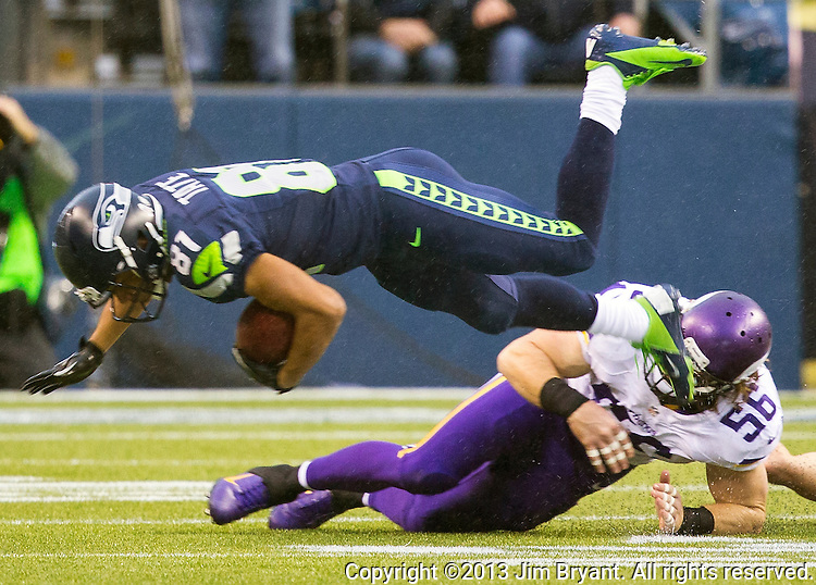 Seattle Seahawks wide receiver Golden Tate is up ended by Minnesota Vikings linebacker Michael Mauti (56) at CenturyLink Field in Seattle, Washington on  November 17, 2013.  The Seahawks beat the Vikings 41-20.  ©2013.  Jim Bryant. All Rights Reserved.