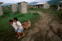 Children in the new settlement of Limón de la Cerca play outside temporary shelters. Entire villages were washed down swollen rivers as Hurricane Mitch lingered over the country in October 1998.