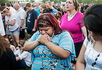 Stephanie Velazquez  (cq), 22, from Aurora, prays during a vigil for the 12 victims of the mass shooting at the Aurora Century 16 movie theater at the Aurora Municipal Center, in Aurora, Colorado, Sunday, July 22, 2012. Suspect James Holmes, allegedly went on a shooting spree and killed 12 people and injured 59 during an early morning screening of 'The Dark Knight Rises.'..Photo by MATT NAGER