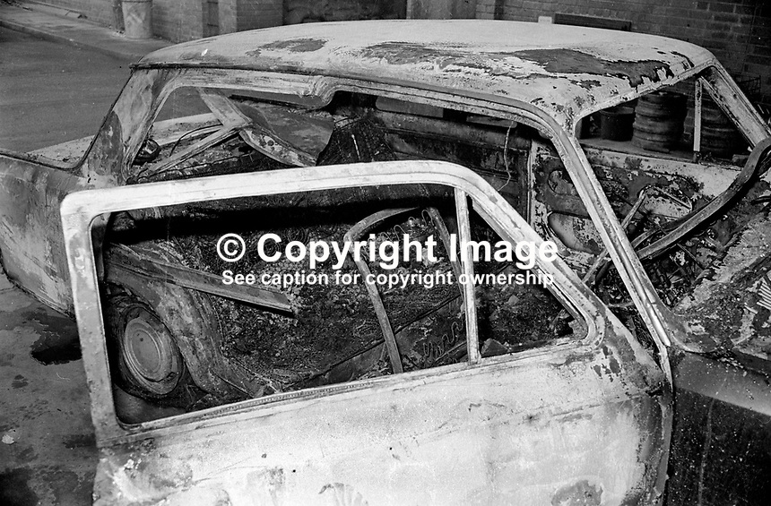 Burnt-out shell of a car in which two bodies were found at Downing Street, off Shankill Road, Belfast, N Ireland on 23rd January 1977. The victims, stabbed &amp; shot, were Thomas John Boston, Crumlin, Co Antrim and John Joseph Lowther, a native of Co Mayo, Rep of Ireland, but who had been living in Bolton, Lancashire, UK, for 20 years. Boston, a Protestant and an Orangeman, and Lowther, a Roman Catholic, worked for the same building company, had been out drinking together and ended up in a loyalist club on the Shankill Road. The loyalist gang which picked them up included senior UDA members, Jim Craig and Arthur Bettice, who were later shot by their own organisation. 197701230025.<br />