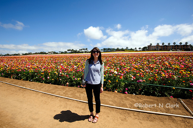 Young woman standing in front of the Ranunculus fields in Calrsbad