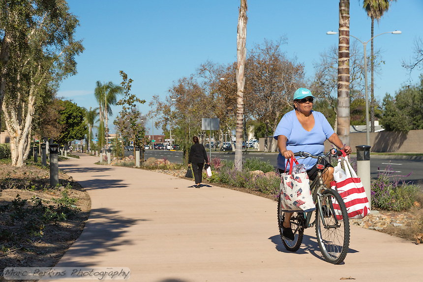 A bicyclist carrying two large shopping bags on her handlebars rides toward the camera while a walker also carrying two shopping bags walks away from the camera along the Harbor Boulevard Cornerstone Bike Trail in Costa Mesa, California under a clear blue sky.  The two women are clearly comfortable using the trail for their errands.  The landscaping of the path, including a diversity of plants and rocks, can be seen behind the people.  The landscape architecture work on the project was done by David Volz Design.